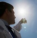 Scientist holding flask to sun