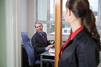 Male Businessman Talking to Female in Doorway