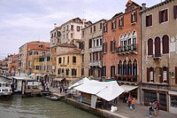 Group of people walking on a promenade along a canal, Venice, Italy