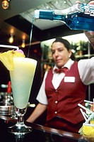 Germany - Cruise down the Rhine river on board of Rhine Emerald boat. Barmaid pouring cocktail