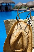 Close-up of a straw hat and a straw bag at the poolside, Cancun, Mexico