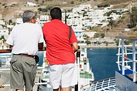 Rear view of two men leaning against a railing of a yacht and looking at view, Patmos, Dodecanese Islands, Greece