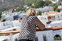 Rear view of a mid adult woman leaning against a railing and looking at a view, Patmos, Dodecanese Islands, Greece