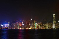 Skyscrapers lit up at night in a city, Victoria Harbor, Hong Kong Island, Hong Kong, China