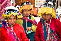 Portrait of three girls in a market, Pisaq, Urubamba Valley, Peru