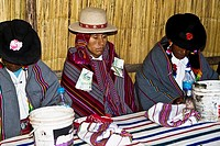 Two mature men sitting with a groom at a table, Taquile Island, Lake Titicaca, Puno, Peru
