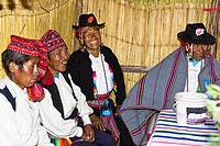 Four people sitting and smiling, Lake Titicaca, Taquile Island, Puno, Peru