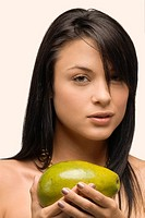 Portrait of a young woman holding an avocado