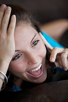 Close-up of a young woman talking on a mobile phone and laughing