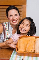Portrait of a girl and her mother smiling with a tray of breads in the kitchen