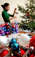 woman decorates a christmas tree, christmas decorations in foreground