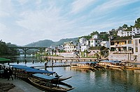 Boats docked by harbor while people walking on jetty in river, old city near Tuo River, Fenghuang, Xiangxi Prefecture, Hunan Province, People's Republ...
