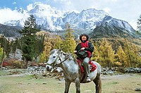 Tourist sitting on horse, Siguniang Mountain, Xiaojin County, Aba State, Sichuan Province of People´s Republic of China, FOR EDITORIAL USE ONLY