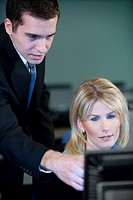 Two business people looking at a computer monitor