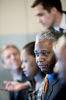 Focus on African American business man in group meeting