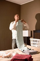 Young man folding towels