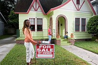 Portrait of family outside house with woman standing by For Sale sign