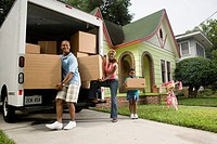 Portrait of a family unloading boxes from moving truck