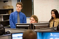 Young office workers gathered around computer screen