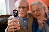 Senior couple photographing themselves with cell phone camera