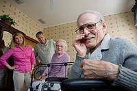 Elderly man whispering to camera with spouse and adult children in background