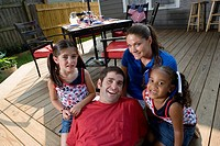 Family on backyard patio with 4th of July decorations in background