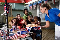 Two families on backyard patio enjoying a cookout on the 4th of July