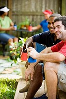 Two men sitting on steps of backyard patio enjoying cold beverages