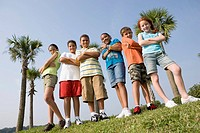 Portrait of children with folded arms standing abreast at a playground