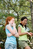 Two girls laughing together at a park