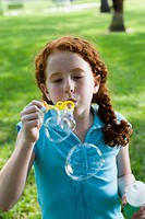 Close_up of a girl blowing bubbles at a park