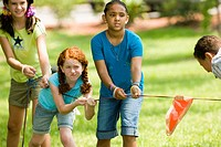 Three girls pulling hard at tug_of_war at a park