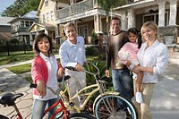 Family with young child standing with neighbors in front of house