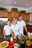 Portrait of a couple with their son having breakfast in the kitchen