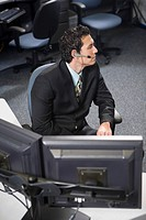 Office worker in a suit with headset sitting at his desk