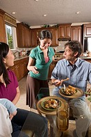 Teenage Asian_Caucasian girl serving a home_cooked Asian dinner to her family