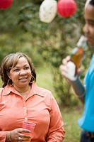 Mature woman watching son drink bottle of soda