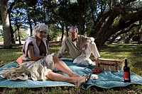Mature couple sitting on a picnic blanket in a park