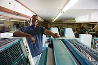 Portrait of a blue_collar man standing behind a printing machine
