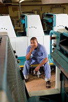 Portrait of a man in coveralls sitting in front of a printing machine