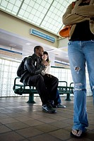 Young inter_racial couple sitting on a bench at a public train station