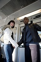 Portrait of a cheerful young inter_racial couple traveling in a mass transit train