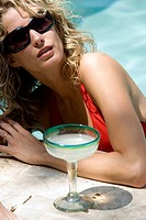 Close_up of a young woman in a swimming pool with a margarita