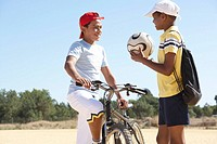 Two boys 11-13 talking on beach, one with bicycle, other with football