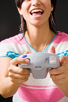 Young woman playing video game, holding joypad, mid section