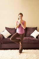 Woman performing yoga tree pose in living room at home