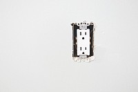 Broken electrical socket on white wall