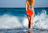 Woman in bikini standing in surf holding red book, rear view, mid section