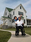 Senior woman with grandson 10-11 riding on wheelchair wearing helmets, portrait