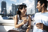 Mid adult couple on yacht drinking wine, cityscape in background